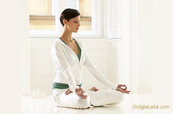 Дівчина сидить в позі дзен - вдома виконує вправи йоги для схуднення
